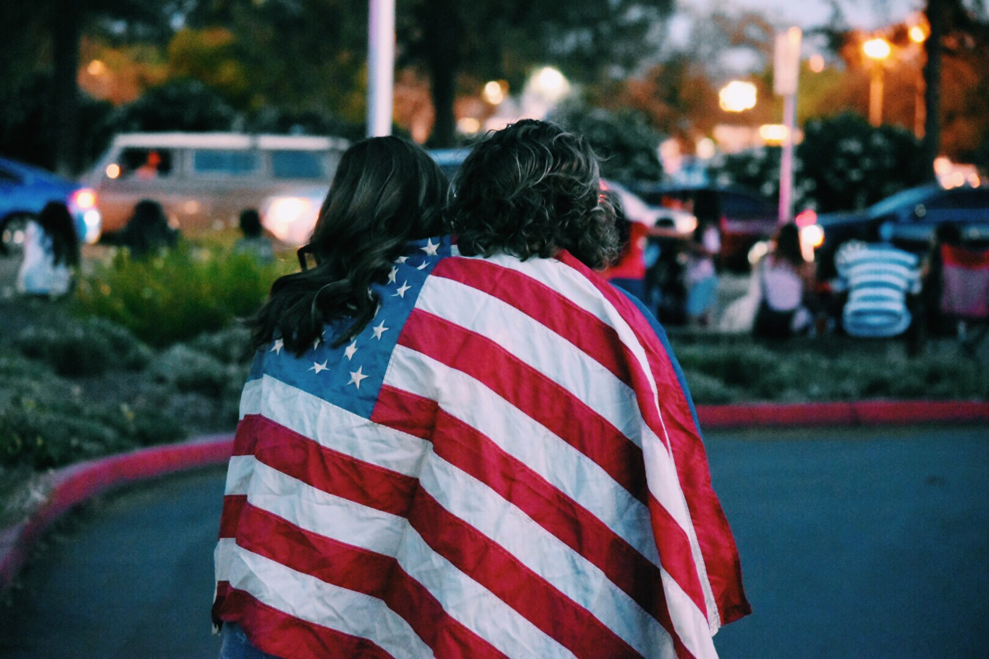 two people walk together with an American flagged draped over their shoulders